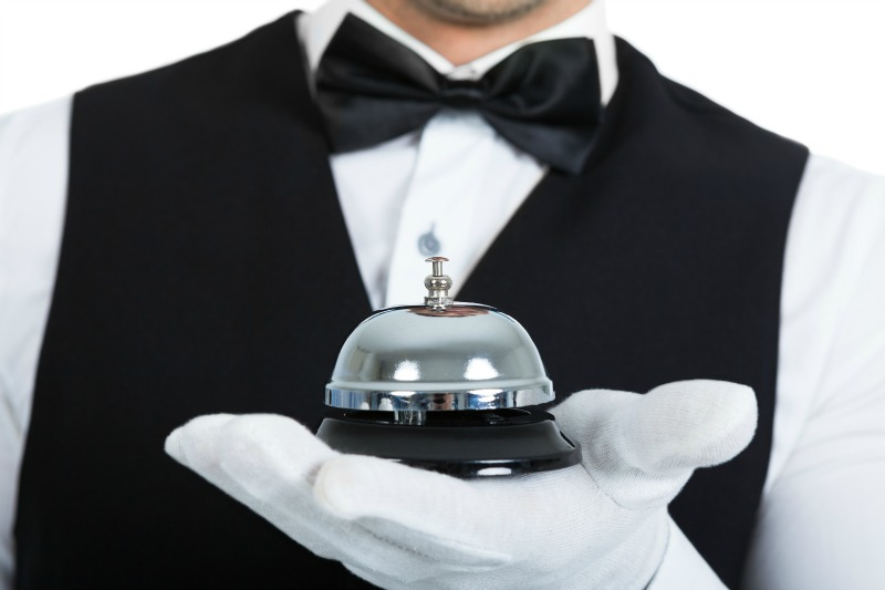 Midsection of young butler holding service bell over white background ** Note: Shallow depth of field